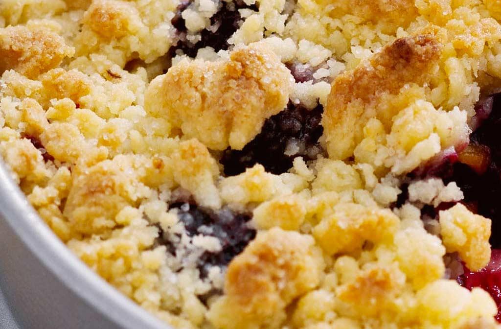 Airfryer recept: zwarte bessen en abrikozen crumble taart in een witte schaal