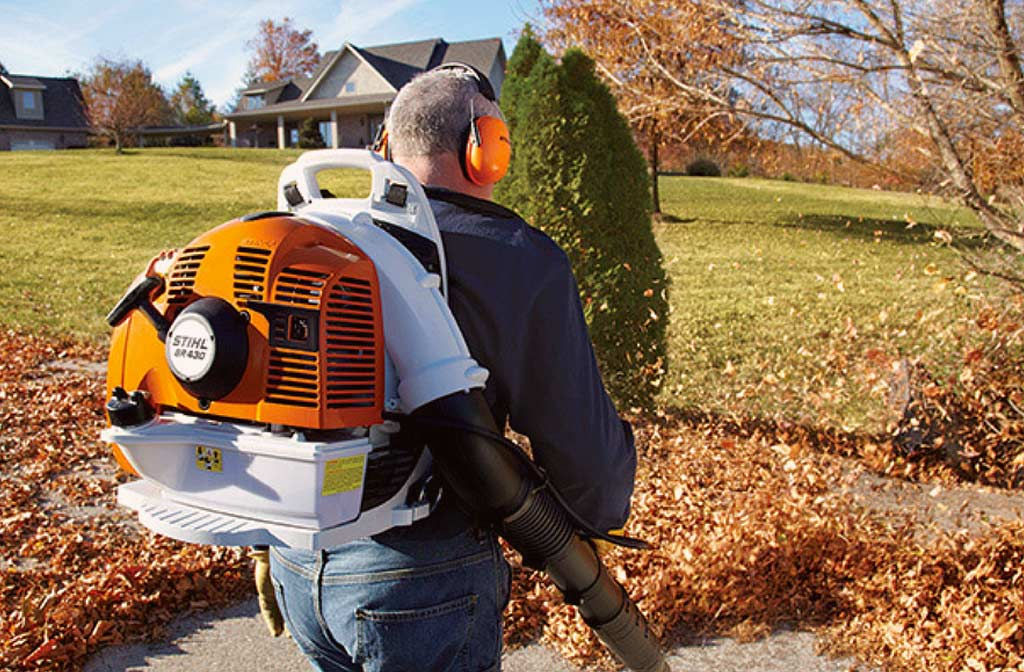 Man met gehoorbescherming gebruikt een rugzakmodel bladblazer op gevallen bladeren