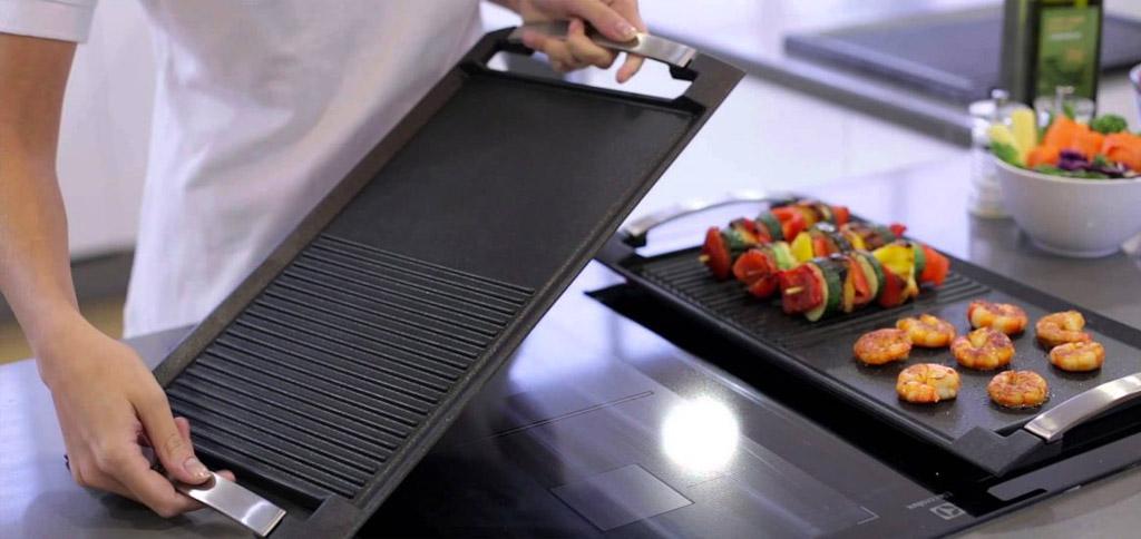 Grillen op inductie met een langwerpige grillplaat met handvaten